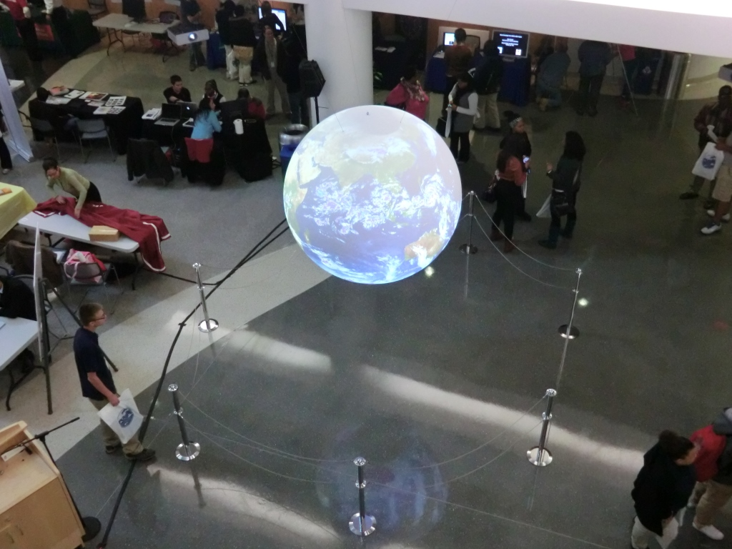 Photography of GISday at the National Weather Center. In the center earth hologram