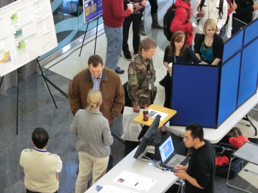 Photography of GISday at the National Weather Center. A close up view of attendees interacting with expositors is shown